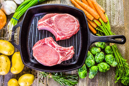 starchy food: Organic pork lion chops of thick cut on cast iron frying pan.