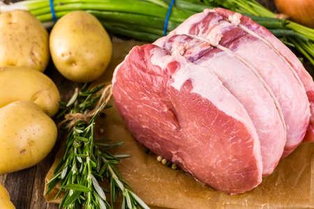 allium cepa: Organic pork lion roast with rosemary on wood farm table.
