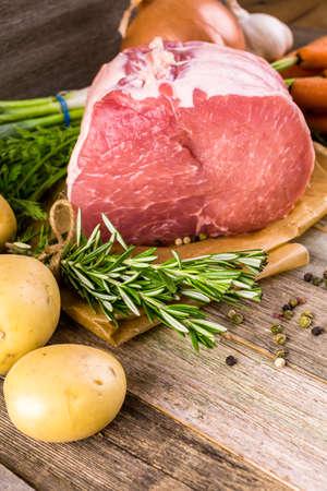 etymology: Organic pork lion roast with rosemary on wood farm table.