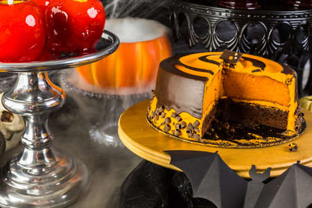taffy: Table with colored candy apples and cake for Halloween party. Stock Photo