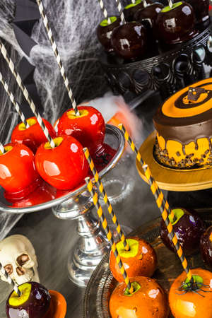 taffy apple: Table with colored candy apples and cake for Halloween party. Stock Photo