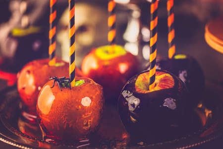 Table with colored candy apples and cake for Halloween party. Stock Photo