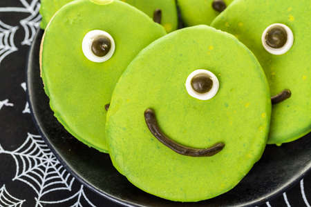 baked treat: Alien cookies with green icing prepared as Halloween treats. Stock Photo