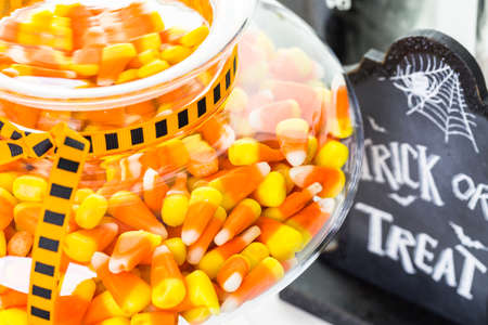 Candy corn in candy jar for Halloween treats.