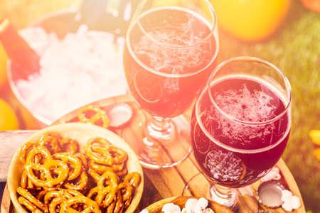 vasos de cerveza: Craft calabaza cerveza en vasos de cerveza con pretzels salados y palomitas de maíz. Foto de archivo