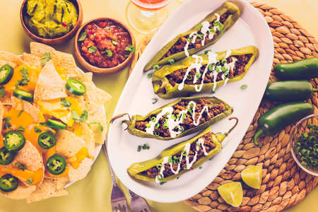 ethnic food: Chipotle beef & bean stuffed chili peppers garnished with sour cream and scallions. Stock Photo