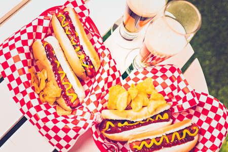 perro caliente: A la parrilla perros calientes con mostaza y ketchup en la mesa con cerveza de barril. Foto de archivo