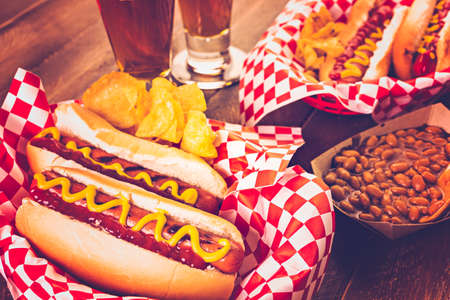 hotdog: Grilled hot dogs with mustard and ketchup on the table with draft beer.