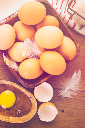 Fresh farm eggs, milk and butter on wood table.