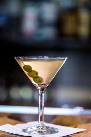 Bartender making martini with olives in Italian restaurant.