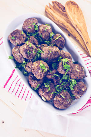 serving dish: Serving large Italian meatballs in a white serving dish for dinner. Stock Photo