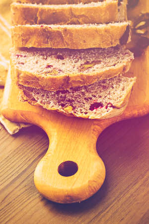 Freshly baked sliced sourdough cranberry nut bread on the table.