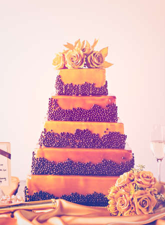 tiered: Gourmet tiered wedding cake as centerpiece at the wedding reception.