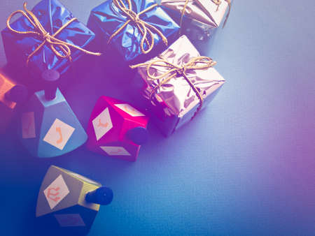 dreidels: Colorful dreidels with presents on blue background. Stock Photo