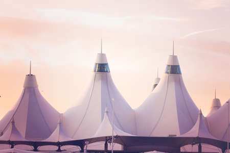 denver at sunrise: Tents of DIA at sunrise. Denver International Airport well known for peaked roof. Design of roof is reflecting snow-capped mountains. Stock Photo