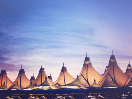 colorado rocky mountains: Glowing tents of DIA at sunrise. Denver International Airport well known for peaked roof. Design of roof is reflecting snow-capped mountains.
