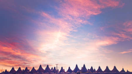 denver at sunrise: Glowing tents of DIA at sunrise. Denver International Airport well known for peaked roof. Design of roof is reflecting snow-capped mountains.