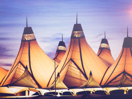 peaked: Glowing tents of DIA at sunrise. Denver International Airport well known for peaked roof. Design of roof is reflecting snow-capped mountains.