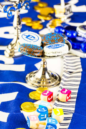 Colorful Hanukkah dreidels and gold gelt on the table. Stock Photo