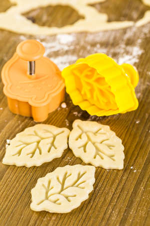 Cutting out Autumn leafs with cookie stamper to decorate pumpkin pie.