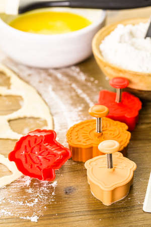 Cutting out Autumn leafs with cookie stamper to decorate pumpkin pie. Stock Photo - 48224887