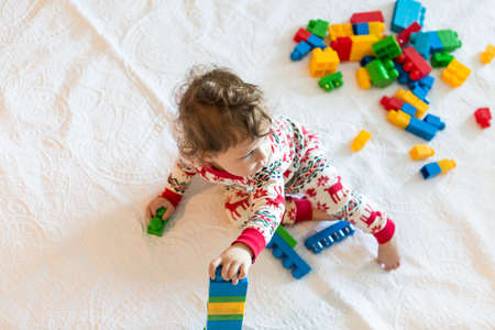 pj's: Cure toddler girl playing with colorful blocks on Christmas day. Stock Photo