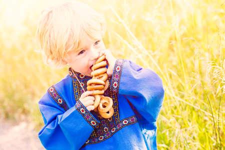 niños rubios: Niños rusos en trajes tradicionales rusos juegan en el bosque.