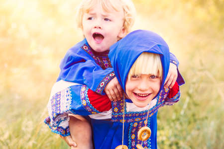 Russian children in traditional Russian costumes playing in the forest.