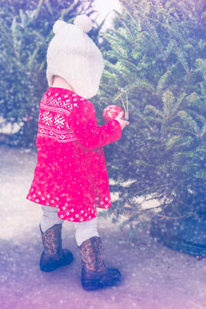 12 13: Cute baby girl in red Scandinavian dress at the Christmas tree farm. Stock Photo