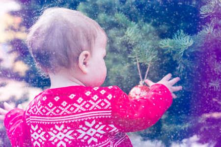 scandinavian girl: Cute baby girl in red Scandinavian dress at the Christmas tree farm. Stock Photo