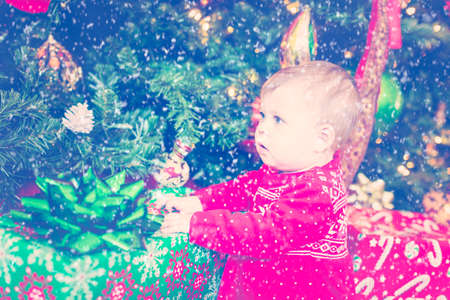 scandinavian girl: Cute baby girl in Scandinavian red dress next to Christmas tree.