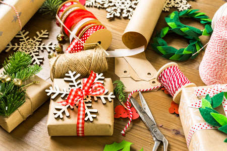recycling: Wrapping Christmas gifts in recycled brown paper with vintage style at home.