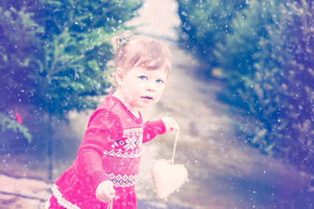 Cute toddler girl looking for Christmas tree. Stock Photo