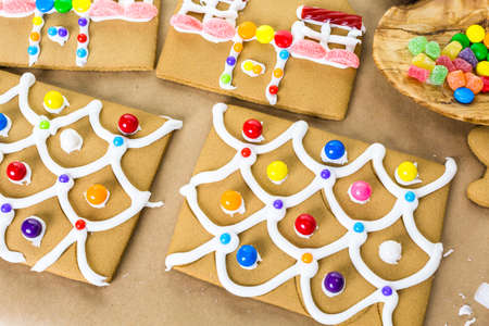 baked treat: Decorating gingerbread house with royal icing and colorful candies.