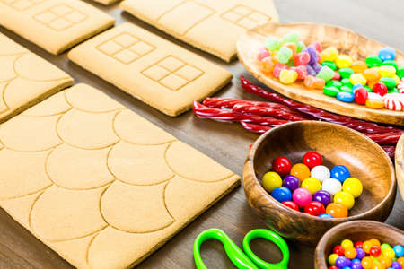 gingerbread house: Decorating gingerbread house with royal icing and colorful candies.