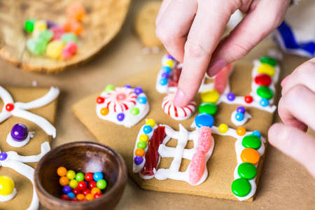 decorating: Decorating gingerbread house with royal icing and colorful candies.