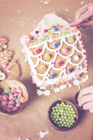 baked treat: Building gingerbread house for Christmas. Stock Photo