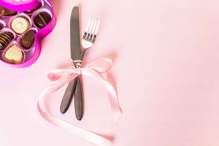 Utencils with pink ribbon on pink background.