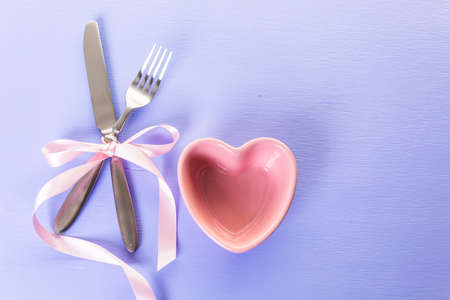 utencils: Utencils with pink ribbon on blue background.