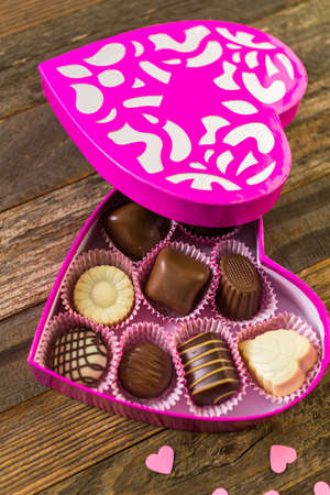 heart shaped box: Chocolates in heart shaped box on rustic wood table.