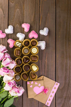 Assorted chocolated with pink roses on wood table. Imagens