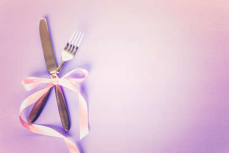Utencils with pink ribbon on blue background.