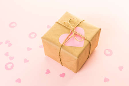 Gift box wrapped in recycled paper and decorated with pink heart.