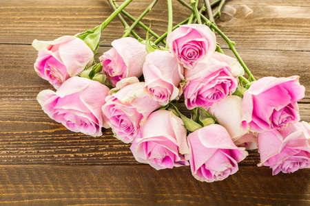 homely: Pink roses on wood table.
