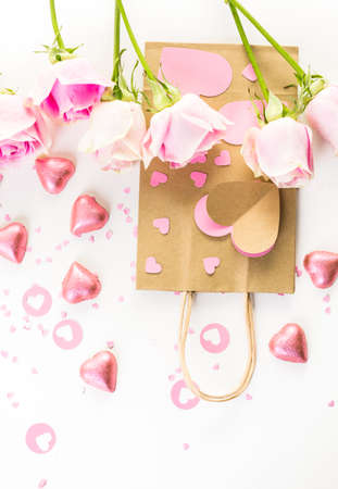 nad made: Pink roses and hand crafted gift bag on a white background.