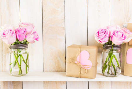 nad made: Bouquet with pink roses in mason jar on wood shelf.
