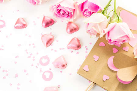 hand crafted: Pink roses and hand crafted gift bag on a white background.