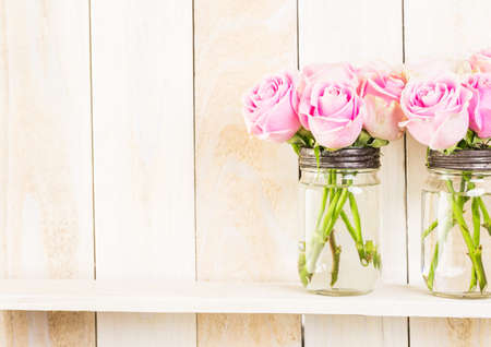 glass jar: Bouquet with pink roses in mason jar on wood shelf.