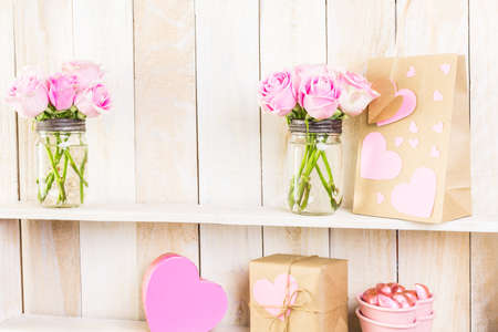 wood shelf: Bouquet with pink roses in mason jar on wood shelf.