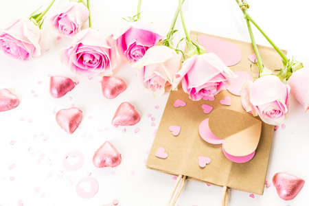 mode made: Pink roses and hand crafted gift bag on a white background.